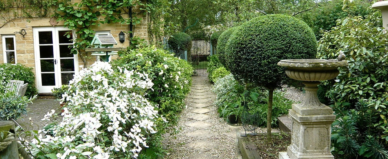 A-traditional-Cotswold-garden-of-rooms-around-a-stone-cottage
