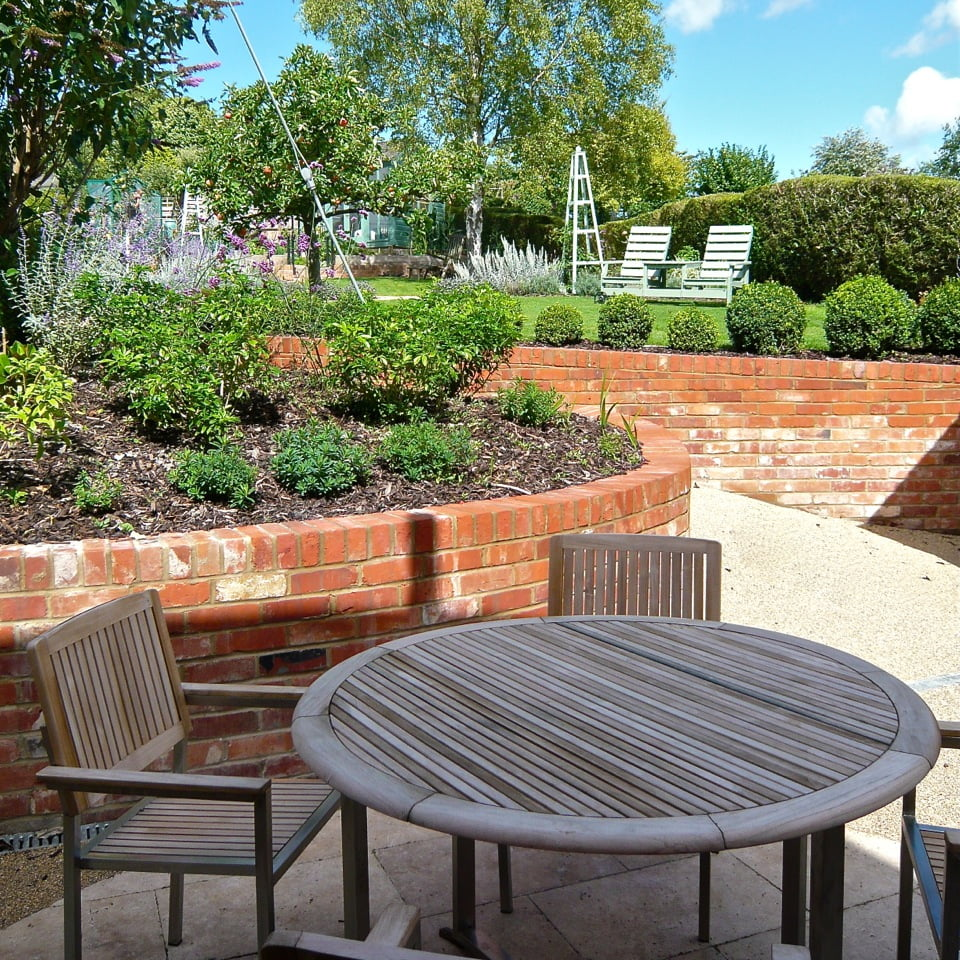 We used brick retaining walls here to create a terrace area at the lower level of this sloping garden. By curving them they look friendly & lead the way up the slope to the main garden