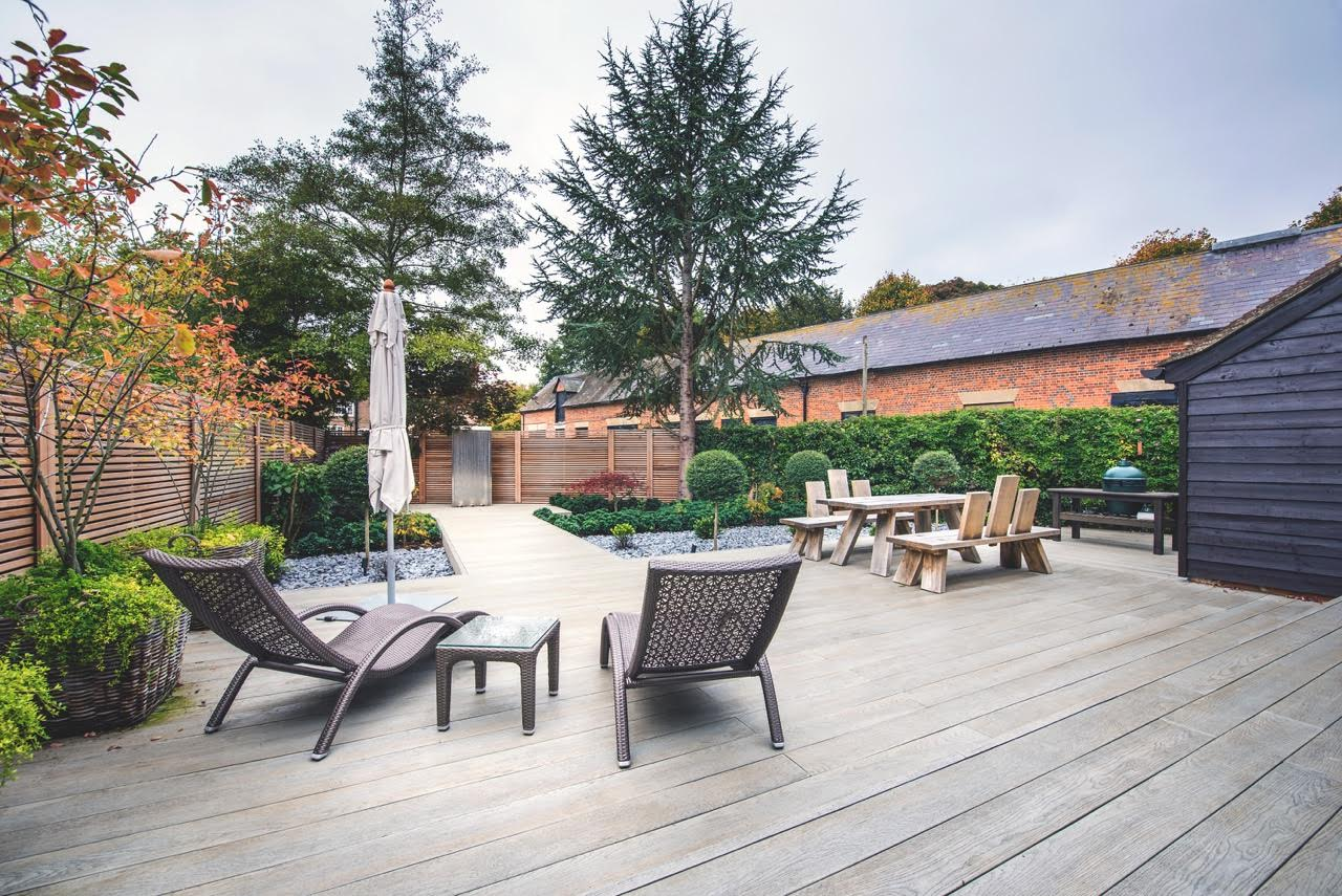 This is a modern garden design for a barn conversion with a water feature & strip fencing
