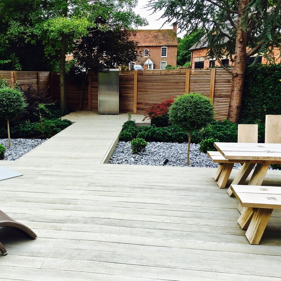Lovely boardwalk & water feature with topiary in this modern garden