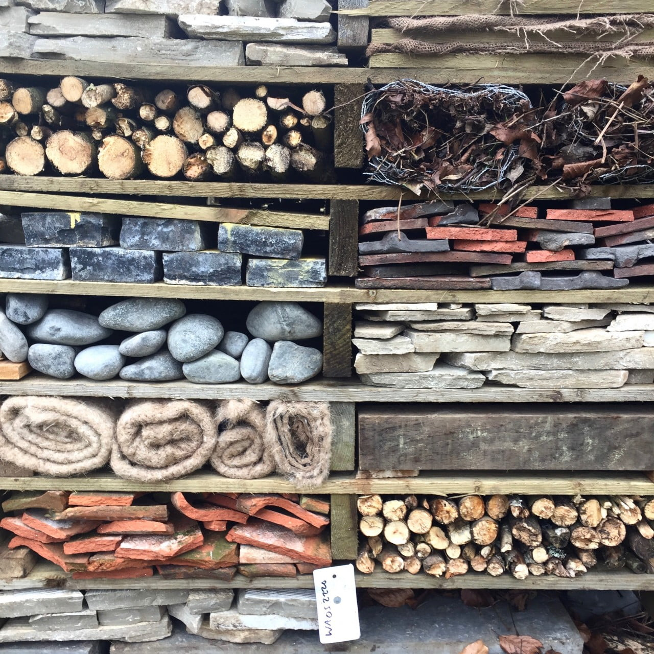 This is a bug hotel made by The Garden Design Co Ltd for a woodland garden out of recycled pallets
