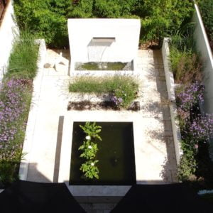 A simple contemporary courtyard garden in Henley on Thames by Jo Alderson Phillips featuring white rendered walls, a pool & water wall