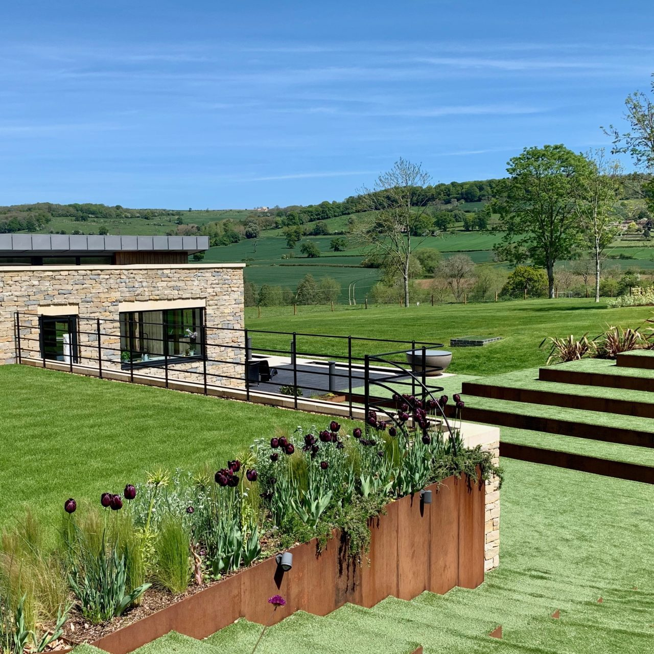 Corten steel suports adding architectural deail to this contemporary Cotswold garden
