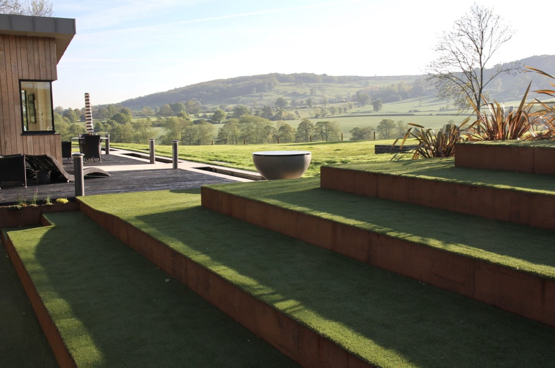 Corten steel steps & faux turf in this contemporary Cotswold scheme