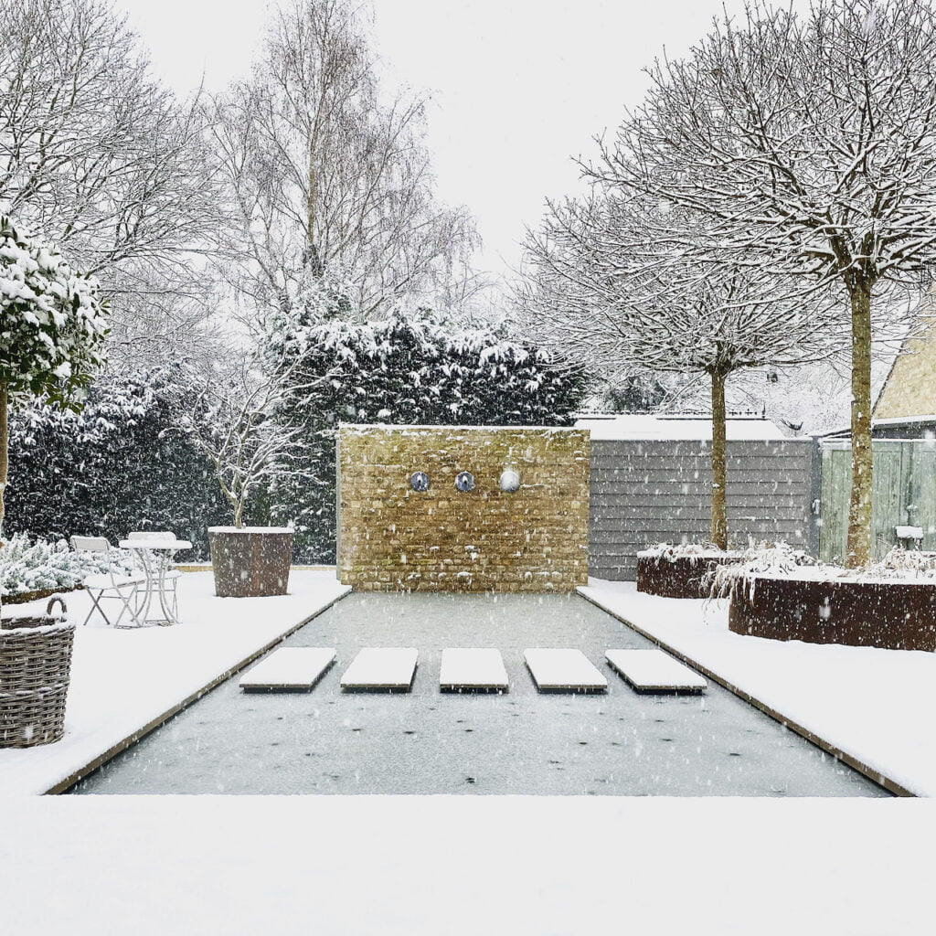 Our snowy courtyard by Jo Alderson Phillips. The Cotswold stone wall looks pretty against the white backdrop & the stepping stones really stand out in the pool