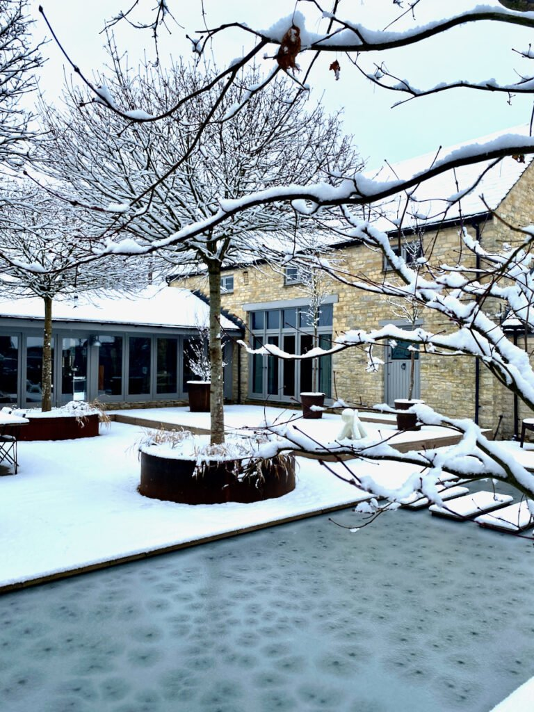 view across the frozen pond to the Cotswold barn beyond. Garden design by Cotswold garden designer Jo Alderson Phillips